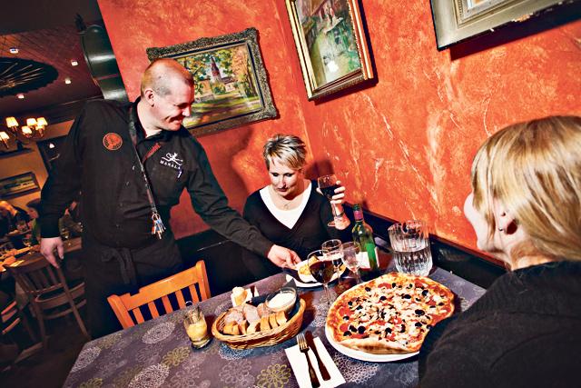 Vuoropäällikkö Juha  Piispanen tarjoilee Manalassa Eija Joensuulle etanoita ja Minna Luomalle pitsaa.