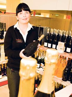 Salomonkadun Alkon myyjä Suvi Sinivirta ja 225 eurolla samppanjaa.