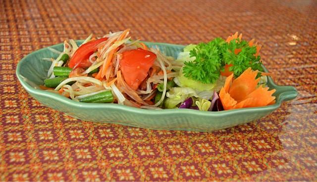 Vihreä suikaloitu papaijasalaatti, chiliä, porkkanoita ja maapähkinöitä. Makuelämys tulisen ruoan ystävälle.