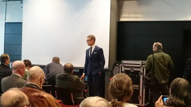 Alexander Stubb pitää vaalitilaisuutta ja samalla TesPack -aurinkoenergialaukun fani nosti tuotesijoittelulla (ilman lupaa??) tuotteen kuviin.
