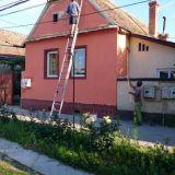 Maalari maalaa taloa Romaniassa.