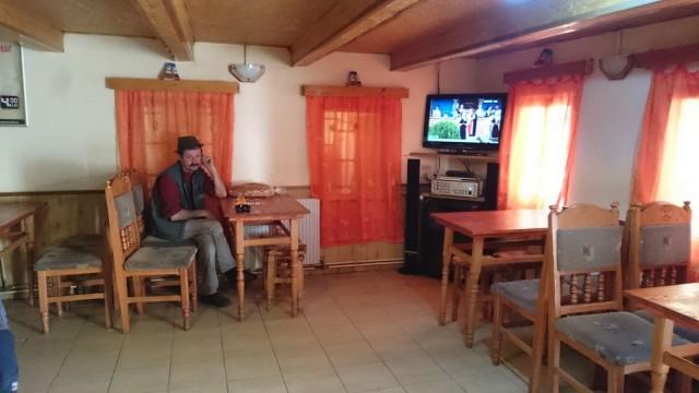 Romanialainen istuskelee kahvilassa. Televisiosta tulee paikallista musiikkia.