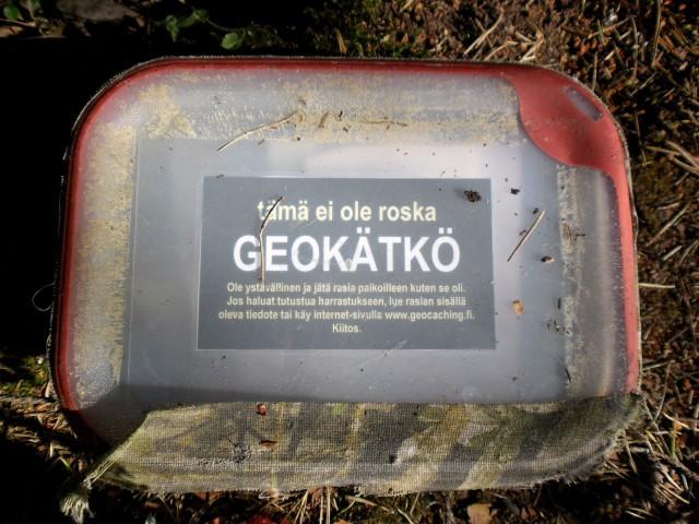 Esimerkki kätköpurkista: vesitiivis rasia tyypillisellä kätkötiedotteella: ei roska, vaan geokätkö.