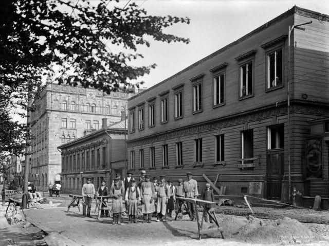 Eteläesplanadi 1907. Työntekijät purkavat kaksikerroksista puutaloa.