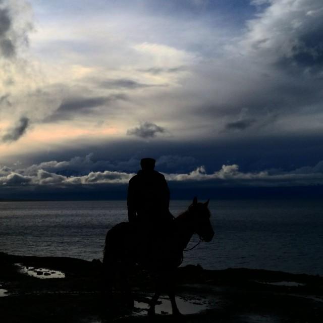 Kiinassa moottoripyörällä. Kohtaaminen Kazakki ratsastajan kanssa. Xingjiang, lake.