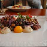 Härkätartar - Dijonmajoneesia, keltuaista ja rapeaa sipulia. / Toisena alkupalana taustalla Västerbotten-juustosalaattia.