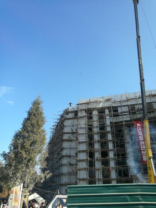 Nyt on käynnissä 200 päivän kampanja. Siloin kaikki tsemppaavat ja tsemppauskuoro käy työmaiden edessä soittamassa. Rakennukset valetaan paikallaan. Rakennustelineet rakennetaan käsin, laudoista.