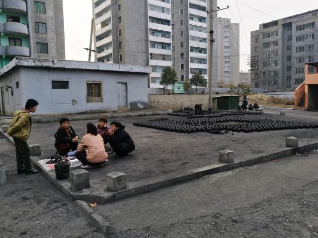 Kivihiili sekoitetaan (käsin tietenkin) mutaan, jotta saadaan sopivia poltettavia brikettejä ja talot pysyvät lämpiminä.