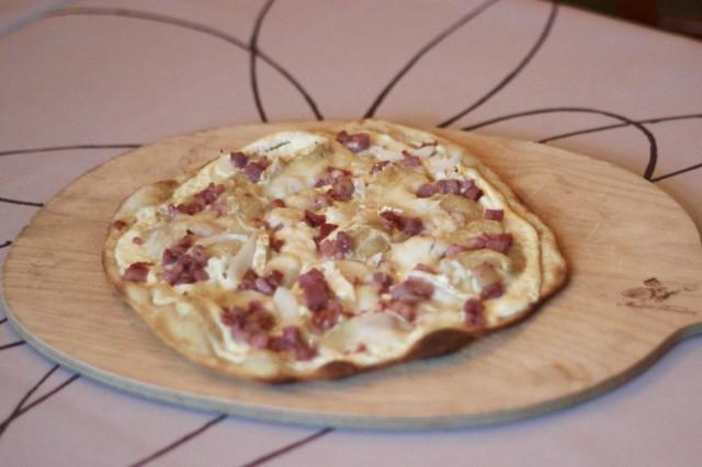 Suosituin tarte flambée on Chèvre & Miel, joka täytetään savupekonilla, vuohenjuustolla ja hunajalla. Herkullinen annos tarjoillaan rennosti puualustalta, ja sen voi syödä sormin.