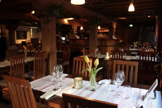 Ruokailutilojen hirsipalkit muistuttavat rakennuksen historiasta. Pöytien kaitaliinat on kudottu Finlaysonin ylijäämätekstiileistä, ja ne luovat ravintolaan rentoa hygge-tunnelmaa.