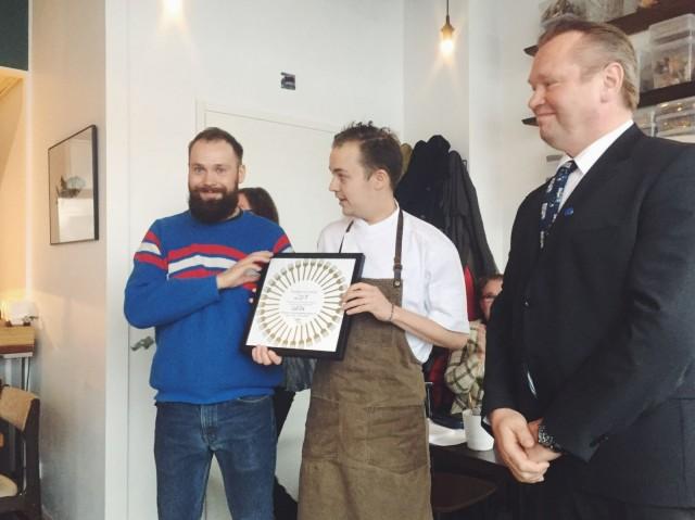 Lauri Kähkönen ja Toni Kostian vastaanottavat Vuoden Ravintola -kunniakirjan Kim Palhusilta.