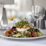 Franklyn SYÖ!-tarjouksiin kuuluva vuohenjuustosalaatti sisältää salaattia, kurkkua, tomaattia, marinoitua punasipulia, varrellisia kapriksia, mummonkurkkua, paahdettuja kikherneitä sekä punajuurivinaigrettea ja yrttiöljyä. Annos on vähälaktoosinen ja