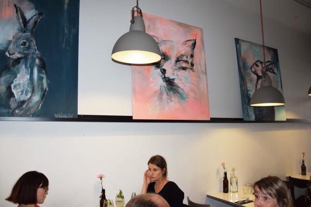 Seiniä kiertävät Nora Helsingin maalaukset.