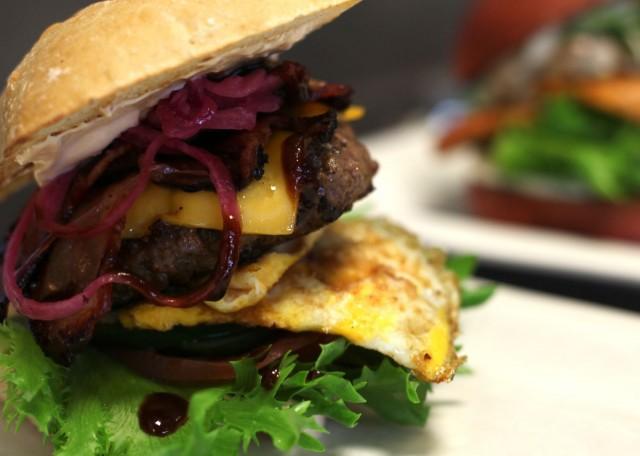 Uudistuneesta house burgerissa on BBQ-kastiketta, cheddarjuustoa, paistettu luomumuna, marinoitua pekonia, sipulia ja mummonkurkkua.