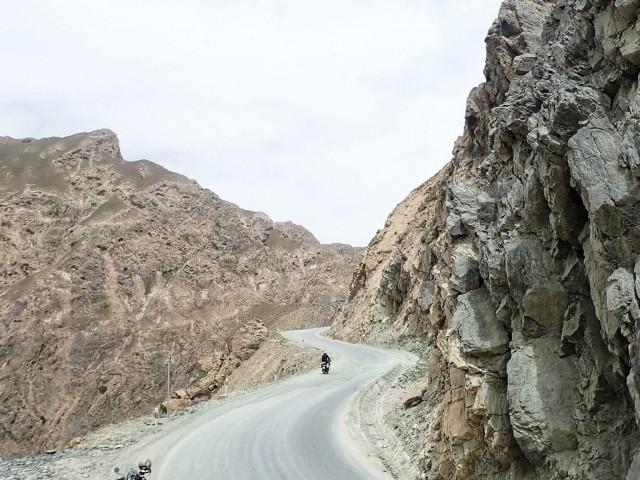 Moottoripyörällä Kiinassa Tiibetin ja Xingiangin rajalla. Oikealla nousee vuori, vasemmalla aukeaa yli kilometrin syvä rotko.