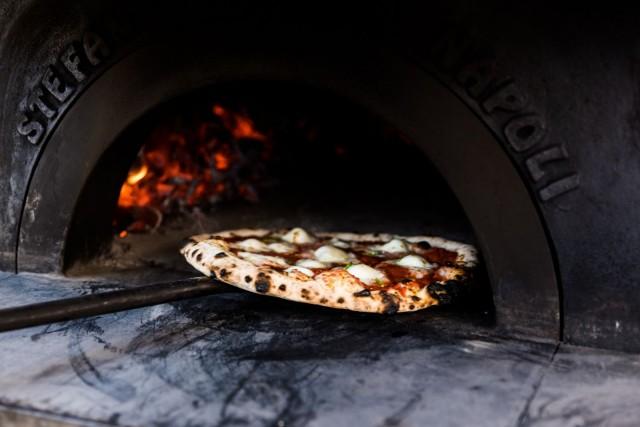 Käsintehty puu-uuni lämpenee 500-asteiseksi ja paistaa pizzan rapeaksi hetkessä.