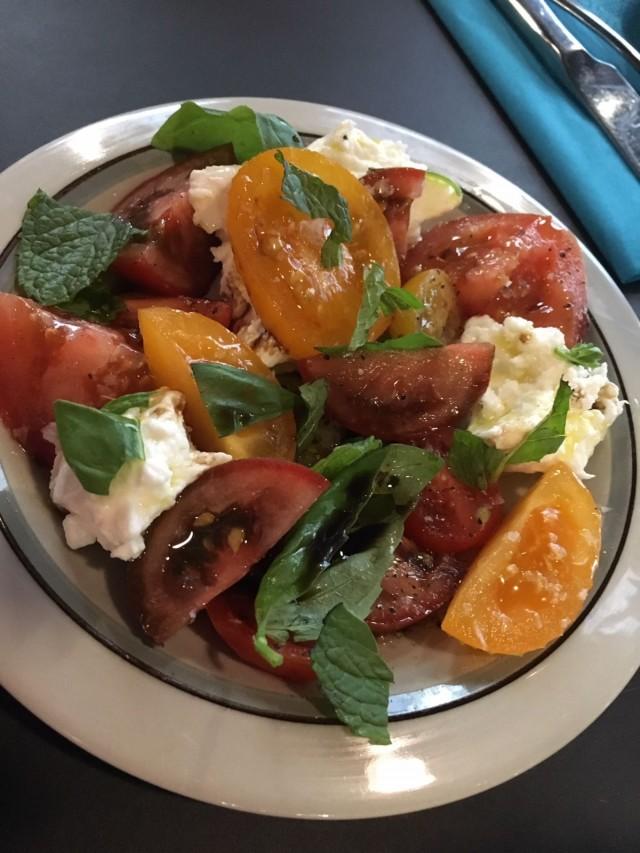 Raikas Caprese-salaatti, jonka kruunaa Mozzarella di Bufala -juusto ja tuore basilika.