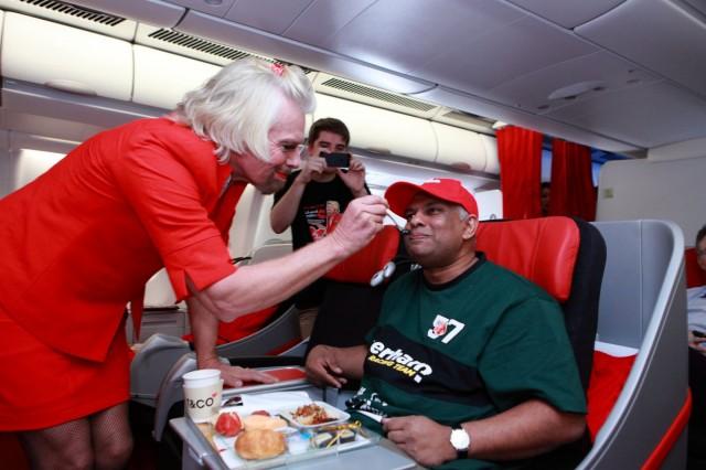 Yritysjohtaja Richard Branson asiakaspalvelemassa Air Asia -yrityksen omistajaa Tony Fernandesia. Branson joutui pukeutumaan naiseksi, koska hänen F1-talli Virgin Formula One Racing Team hävisi Fernandesin Lotus Racing Teamille.