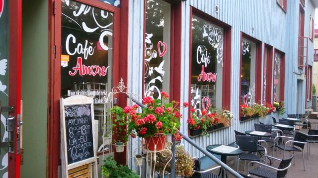 Cafe Amore on perustettu vanhaan siniseen puutaloon, jonka isoja ikkunoita koristaa värikäs kasvillisuus.