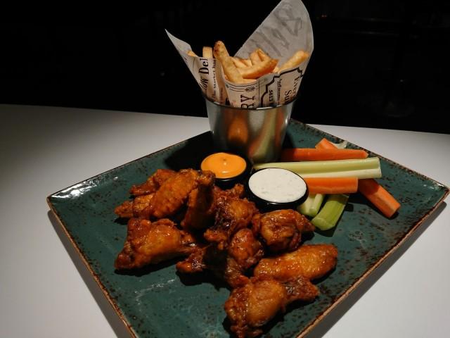 Hiilen friteeratut wingsit tarjoillaan rapeiden maalaisranskalaisten ja dippien kera.