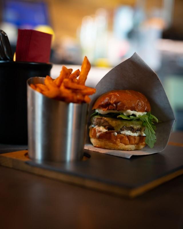 Deluxe Burger & Pizzan Tony's burger: Briossisämpylän välissä grillattua punasipulia, pekonihilloa, Monterey Jack -juustoa, laavakivillä grillattu Black Angus -pihvi, valkosipulimajoneesia ja rucolaa.