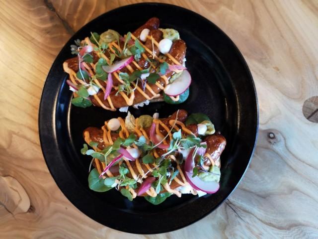 Kumman festarileipä go vegan eli kaksi valkosipulileipää mausteisilla soijachorizomakkaroilla, Kumman omaa sinappia, kiinankaalia, pinaattia, chipotlemajoneesia ja guacamolea.