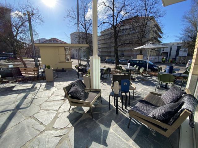 Terassia koristavat oliivinvihreät tuolit ja tummat pöydät sekä kauniit sohvat, nojatuolit ja keinut.
